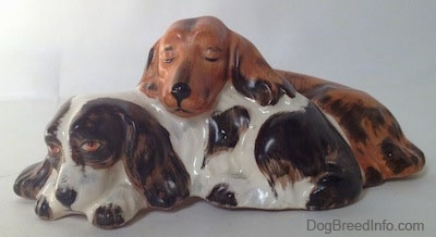 A figurine of two English Cocker Spaniel dogs that are laying down. One of the dogs is sleeping on top of the other dog which is laying down.