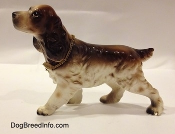 The left side of a brown and white porcelain English Cocker Spaniel figurine. The figurine has a big and long ears.