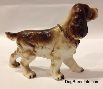 The right side of a brown and white English Cocker Spaniel porcelain figurine. The figurine has fine hair details.