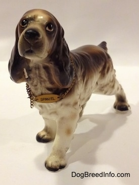 A porcelain brown and white English Cocker Spaniel figurine. The figurine is wearing a collar and on the collar there is a tag that reads - Spaniel.