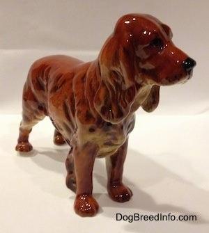 The front right side of a red figurine of a English Cocker Spaniel. The figurine has long legs and small paws.