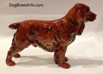 The right side of a red English Cocker Spaniel figurine. The figurine has a short tail.