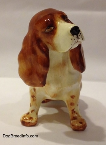 A ceramic figurine of a red and white English Cocker Spaniel in a sitting position figurine. The figurine has great face details.