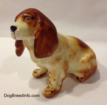 The left side of a red and white ceramic English Cocker Spaniel figurine that is in a sitting position. The side of the figurine has brown brushings to make it look like it has hair.