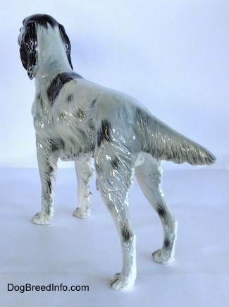 The back left side of a figurine of a black and white English Setter in a standing pose. The figurine has an extended out tail.