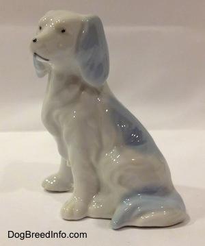 The left side of a bone china white with blue English Setter figurine. The tail of the figurine is attached to its legs.