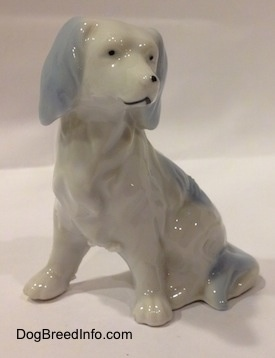 The front left side of a white with blue English Setter figurine. The eyes of the figurine has black dots for eyes.