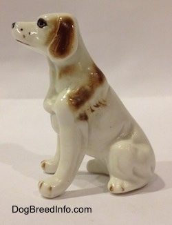 The left side of a white with brown bone china English Setter figurine. The figurine has brown brushings along its body.
