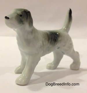 The front left side of a bone china figurine of a black and white English Setter. The figurine has long legs and small paws.