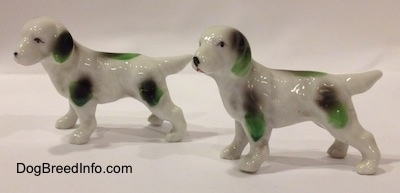 The left side of two bone china English Setter figurines with green and black markings. Both of the figurines tails are in the air.