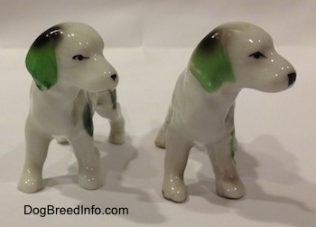 Two English Setter bone china figurines that are white with green and black. The figurines have large black and green ears.