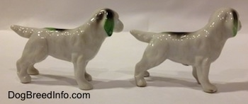 Th right side of two bone china white with green and black English Setter figurines. The figurines have a long body, long legs and short paws.