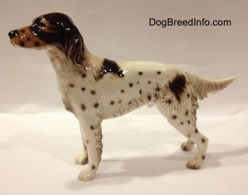 The left side of a brown and white English Setter porcelain figurine. The figurine has hair details along the trim of its body.