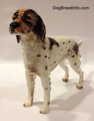The front left side of a porcelain figurine of a brown and white English Setter. The figurine has great chest hair details.