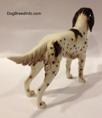 The back right side of a brown and white English Setter porcelain figurine. The figurine has a detailed body.