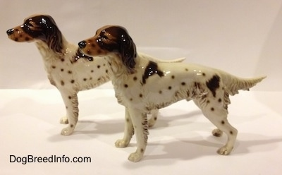 The left side of two porcelain brown and white English Setter figurine. The figurines brown faces and black circles for eyes.