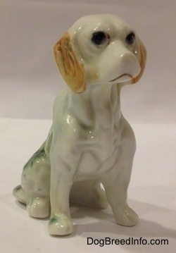 The front right side of an English Setter in a sitting pose figurine. The figurine has big black circles for eyes.