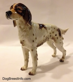 The front left side of a figurine of a brown and white porcelain English Setter. The figurine has a detailed brown face.