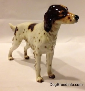 The front right side of a porcelain brown and white English Setter figurine. The figurine has long legs and small brown tipped paws.