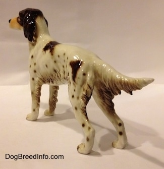 The back left side of a porcelain brown and white English Setter figurine. The tail of the figurine is extended out and it is level with its body.