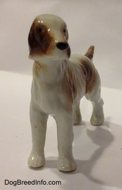 A brown and white bone china English Setter figurine in a standing pose has black circles for eyes.