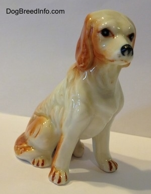 The front right side of a red and white bone china English Setter figurine. The figurine has long legs and small paws.