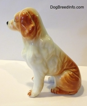The left side of a red and white bone china English Setter figurine. Its hard to tell the difference between the ears of the figurine from its head.