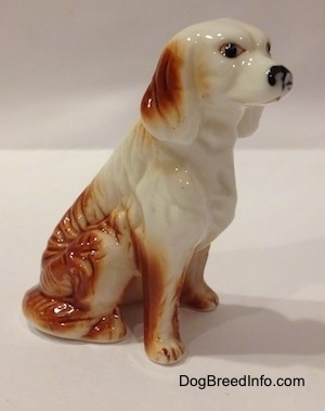 The right side of a bone china red and white English Setter figurine. The figurine has black circles for eyes.