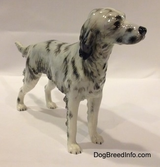 The front right side of porcelain figurine of a white and black English Setter. The figurine has black circles for eyes.
