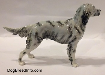 The right side of a white and black English Setter porcelain figurine. The figurine has long legs and small paws.