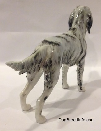 The back right side of a black and white porcelain English Setter figurine. The figurine has hair along the back of its legs.
