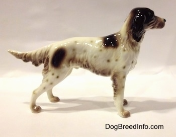 The right side of a figurine of a white with brown English Setter in a standing pose. The figurine has brown spots all over its body.