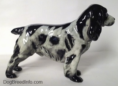 The right side of a black and white figurine of an English Springer Spaniel. The figurine has small black paws.