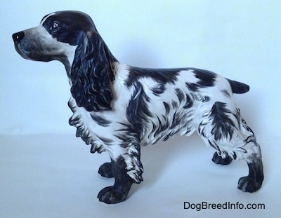 The left side of a black and white English Springer Spaniel figurine with a matte finish. The figurine has a detailed face, it has black eyes a black nose and muzzle.
