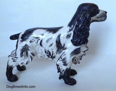 The right side of a figurine of a black and white English Springer Spaniel with a matte finish. The figurine has hair around the edge of its body and legs.