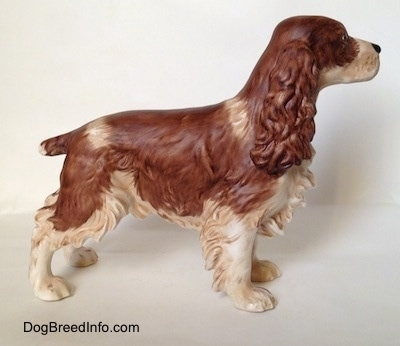 The right side of a figurine of a brown and white English Springer Spaniel in a standing pose with a matte finish. The figurine has long bushy ears,