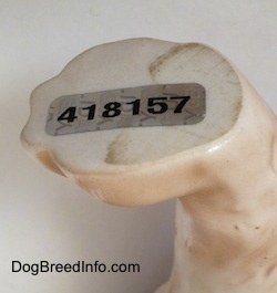 Close up - A sticker that is on the bottom of the left paw of a English Springer Spaniel figurine that reads - 418157.