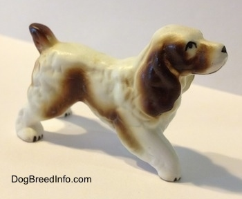 The right side of a brown and white English Springer Spaniel figurine. The figurine has black circles for eyes.