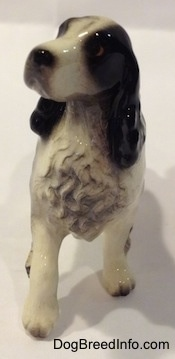 A black with white English Springer Spaniel ceramic figurine. The chest hair of the figurine is very detailed.