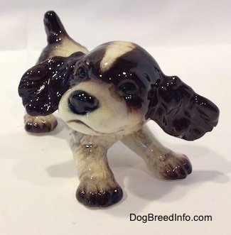 A figurine of a liver and white English Springer Spaniel puppy with its ears flying out. The figurine has black circles for eyes.