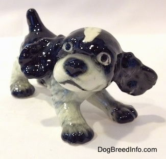 The front right side of a figurine of a black and white English Springer Spaniel puppy in a play bow pose. The figurine has its ears sticking out.