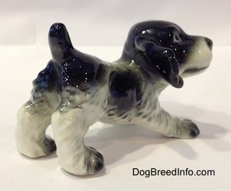 The back right side of a black and white English Springer Spaniel puppy in a play bow pose figurine. The figurine looks like it has ruffled hair on it.