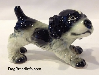 The right side of a black and white English Springer Spaniel puppy in a play bow pose figurine. The figurine has black spots along its side.
