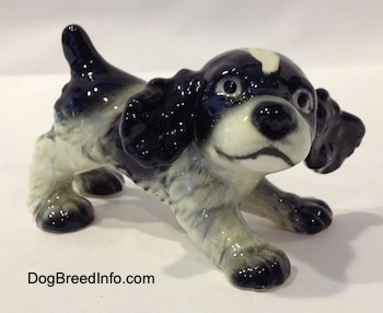 A black and white English Springer Spaniel puppy in a play bow pose figurine. The figurine has black circles for eyes.