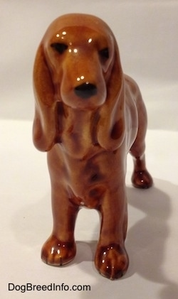 A brown Field Spaniel ceramic figurine. The figurine has black circles for eyes and a nose.