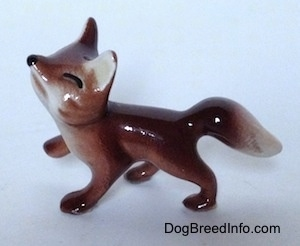 The left side of a Baby Fox figurine that is looking up, it has black lines for eyes and a black circle for its nose.