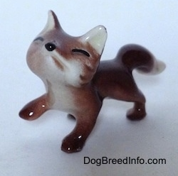 The front left side of a baby fox figurine. The figurine is looking up and it has black small paws.