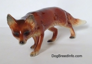 The front left side of a red Fox figurine in a stalking pose. The figurine has black eyes and a black nose and perk ears that stick up to a point.