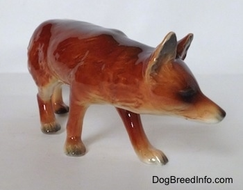 The front right side of a red fox figurine in a stalking pose. The ears of the figurine are standing up in the air.