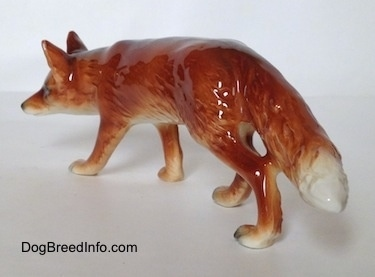 The back left side of a red fox figurine in a stalking pose. The figurine is glossy.